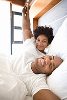 Young couple lying in bed, holding hands and smiling, portrait