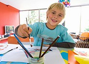Boy 6-8 painting at table, smiling, portrait