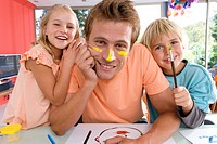 Father with son and daughter 6-8, father with paint on face, smiling, portrait