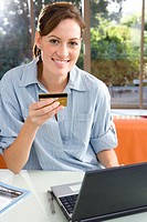Woman holding credit card by laptop, smiling, portrait