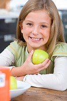 Girl 6-8 holding up green apple, smiling, portrait, close-up