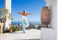 Young woman standing on balcony in tree pose yoga stance, rear view