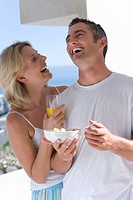 Couple standing on balcony with breakfast, laughing