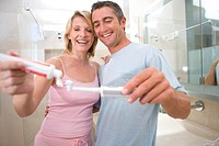 Woman applying toothpaste to toothbrush held by man in bathroom, smiling