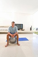 Man sitting on exercise ball in living room, smiling, portrait