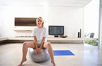 Woman sitting on exercise ball in living room, smiling, portrait