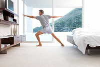 Mature man stretching in yoga stance in bedroom, side view