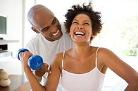 Man smiling at woman lifting weights in living room, woman laughing