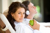 Couple relaxaing on deck chairs, portrait of woman holding green apple, close-up