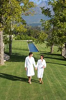Couple wearing white robes, holding hands whilst walking in garden, elevated view