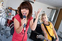 Three teenagers 15-17 in garage band, teenage girl singing in foreground