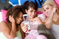 Three teenage girls 15-17 sitting on bed, one taking self portrait with camera phone, smiling