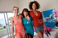 Three teenage girls 15-17 standing on bed in bedroom, smiling, portrait (thumbnail)