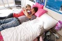 Teenage couple 15-17 kissing on bed, elevated view