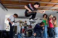 Group of teenagers 15-17 playing music in garage band