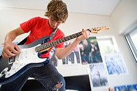 Teenage boy 16-18 playing electric guitar in bedroom, low angle view