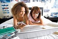 Two teenage girls 16-18 lying on bed using laptop, one holding mp3 player, smiling