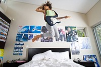 Teenage girl 16-18 playing electric guitar, jumping in air above bed, low angle view