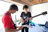 Two teenage boys 16-18 playing guitars in garage