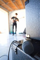Teenage boy 16-18 playing electric guitar in garage, focus on microphone in foreground
