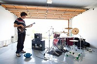Teenage boy 16-18 playing electric guitar in garage by drum kit, side view
