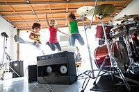 Three teenage girls 16-18 jumping in air by drum kit and amplifiers, smiling, low angle view