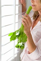 Mature woman holding celery stick, standing by window, side view