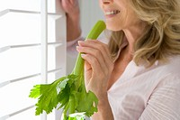 Mature woman holding celery stick, standing by window, smiling, side view