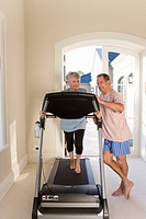 Senior man standing by senior woman running on treadmill indoors, smiling