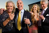 Two mature couples drinking champagne outdoors, laughing