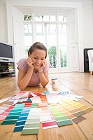 20's woman lying on floor choosing paint colours from paint swatches in living room