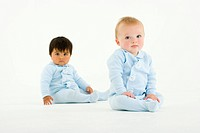 Two baby boys, one Hispanic, one Caucasian, sitting on floor against white background looking into camera,