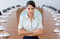 30's businesswoman standing at head of board table
