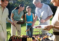 Three generation family standing beside barbecue grill in garden, senior man serving granddaughter 11-13 sausage, smiling