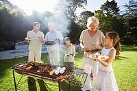Family having barbecue in summer garden, senior woman serving granddaughter 8-10 beside grill, smiling lens flare