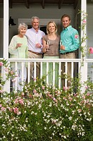 Family standing on veranda overlooking summer garden, holding champagne flutes, smiling, front view, portrait