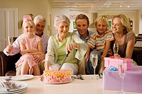 Three generation family sitting on sofa at home, senior woman cutting birthday cake, smiling