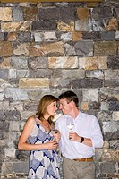 Couple flirting beside stone wall, holding glasses of white wine, smiling