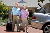 Senior couple leaving house with luggage in tow, approaching parked car with open boot on driveway, smiling