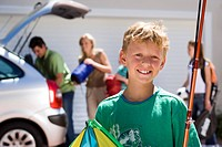 Family loading camping equipment into parked car boot on driveway, focus on boy 8-10 carrying fishing rod and kite in foreground, smiling, portrait