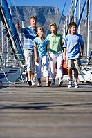 Family walking along harbour jetty, father pointing, smiling, front view