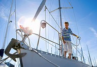 Man standing on deck of moored sailing boat, holding rope lens flare