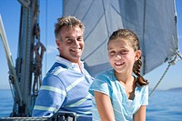 Father and daughter 8-10 sitting on deck of sailing boat, smiling, portrait