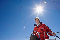Man in red jacket standing at helm of sailing boat out at sea, steering, low angle view lens flare