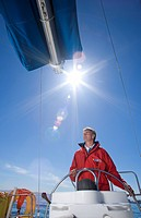 Man in red jacket standing at helm of sailing boat out at sea, steering lens flare