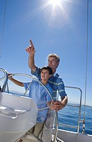 Father and son 8-10 standing at helm of sailing boat out at sea, man pointing direction, boy steering lens flare, tilt
