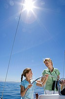 Mother and daughter 8-10 standing at helm of sailing boat out at sea, steering, smiling lens flare, tilt