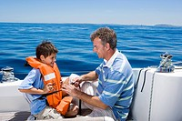 Father and son 8-10 sitting on deck of sailing boat out at sea, boy wearing orange life jacket, man tying strap, smiling, side view