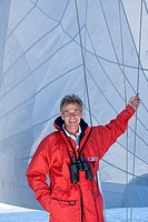 Man in red jacket standing on deck of sailing boat below sail, leaning on rigging, binoculars hanging around neck, smiling, front view, portrait