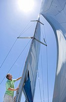 Man standing on deck of sailing boat out to sea, adjusting sail mast rigging, side view, low angle view lens flare